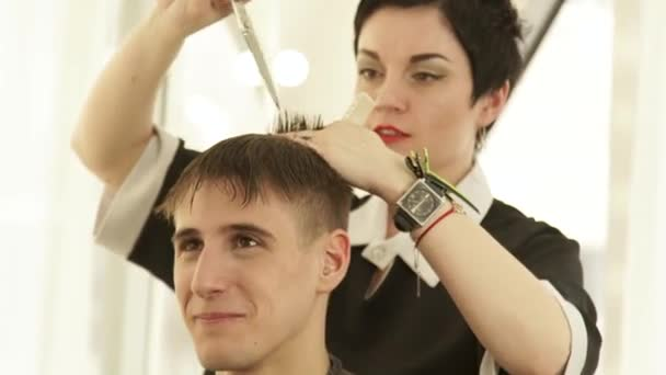 Hair cutting with hairdressing scissors and comb in male barber shop. Haircutter making hairstyle with hairdressing scissors and combing wet hair in beauty studio.