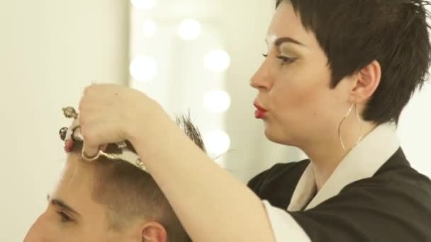 Woman barber combing and cutting hair with professional scissors in hairdressing salon. Close up hairdresser doing hairstyle with hairdressing scissors and comb in barber shop.