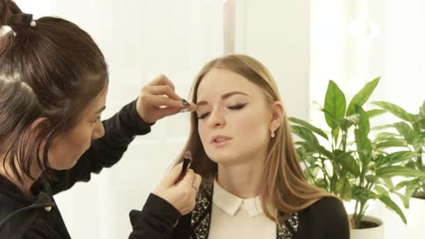 Žena vizážistiku pomocí kosmetiky houba pro opravu make-upu na obličeji krásná žena v šatně. Detailní záběr žena tvář make-up kosmetické Studio