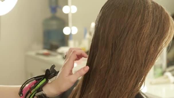 Kadeřník, česání mokrých vlasů před žena účes v kadeřnictví. Zblízka ženský účes v salonu krásy. Příprava na Foukaní dlouhé vlasy kadeřnictví
