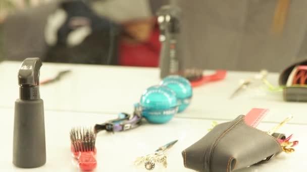 Ženské kadeřník česání a dělení vlasů v kadeřnictví v salonu krásy. Detailní záběr haircutter oprava ženské vlasy s sponka předních zrcátek v kadeřnictví
