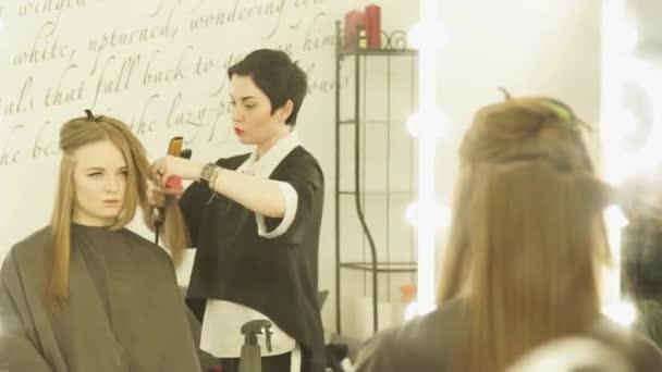Fodrászat frizura haj fogó és szépségszalonban hajkiegyenesítő fésű gyártás. Zárja be a upfemale fodrász hosszú haj hajkiegyenesítő. Nő fodrász, fodrászat