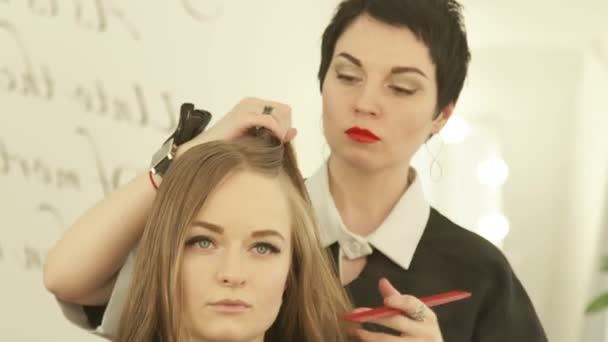 Kadeřníka vlasy před žena účes v kadeřnictví. Detailní záběr ženský účes v salonu krásy.