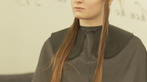 Mladá žena tvář s svorku na vlasy během Foukaní v kadeřnictví zblízka. Ženské vlasy model v studio krásy