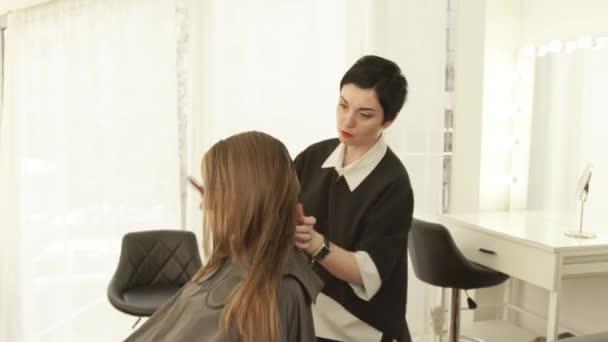 Kadeřnice při česání vlasy žena před řezáním v kadeřnictví. Ženský účes v salonu krásy. Kadeřnicí pracující s klientem zblízka