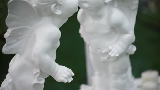 Fehér két csók angyalok szobrok. A kamera mozog az alulról.