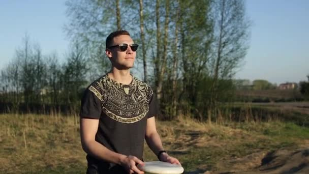 Stylish young man in sunglasses catches a flying disc in nature
