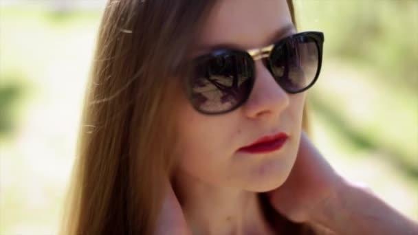 Krásná mladá móda dívka v sluneční brýle s červenými rty opravuje dlouhé vlasy