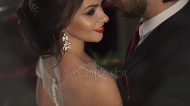 Brutální muž něžně všeobjímající žena v transparentní bílé šaty svadenom. Ona se usmívá široce