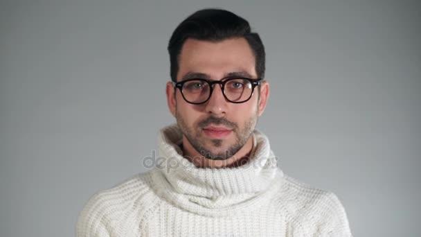 Pohledný mladý muž v stylové brýle se usmívá na fotoaparát a mrkl jedním okem