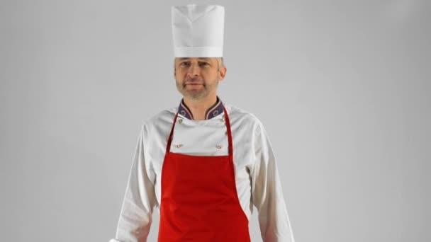 gutaussehender erwachsener Koch dreht sich um, er verschränkt seine Arme mit Messer und Spachtel, er nickt mit dem Kopf auf grauem Hintergrund