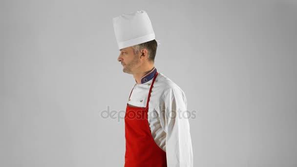 gutaussehender erwachsener Koch dreht sich um, verschränkt seine Arme mit einem Messer und nickt mit dem Kopf auf einem grauen Hintergrund