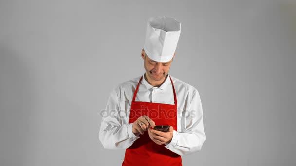 gutaussehender erwachsener Koch tippt auf dem Smartphone, dann blickt er in die Kamera und lächelt auf grauem Hintergrund