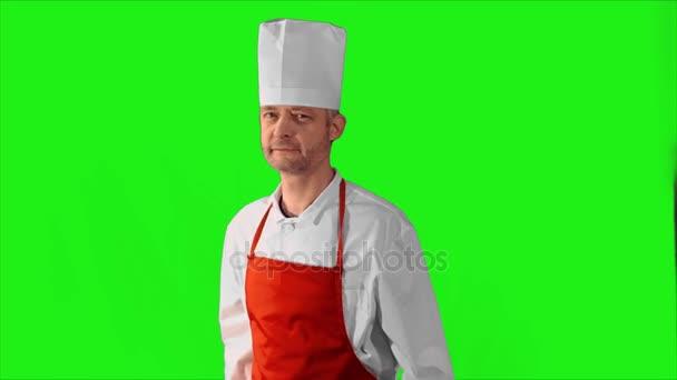 schöner erwachsener Koch dreht sich um, verschränkt die Arme und nickt mit dem Kopf auf grünem Hintergrund