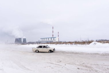 Russia, Novosibirsk - November 30, 2019. An old Russian white car VAZ Zhiguli is driving fast in the drift, turning the wheel, on the road against the background of Smoking pipes of the heat power station in winter.