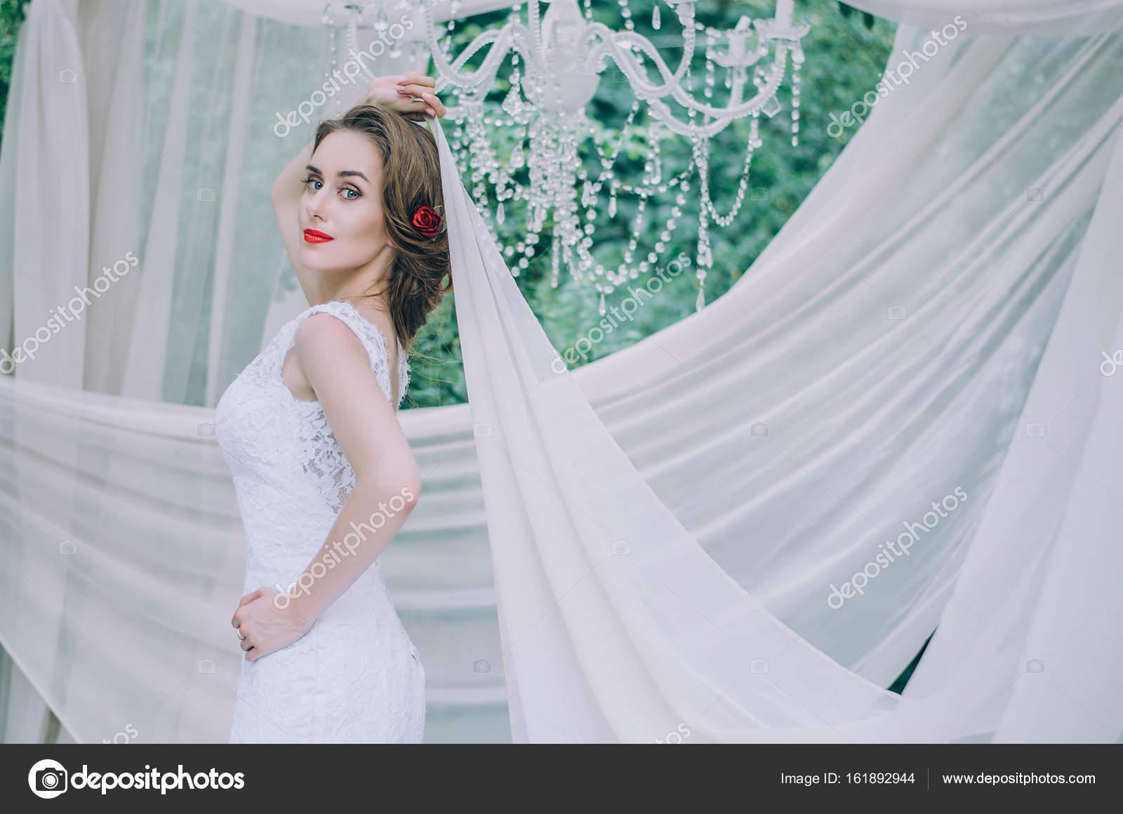 Novia feliz en un vestido largo blanco, con una rosa en el pelo roja ...