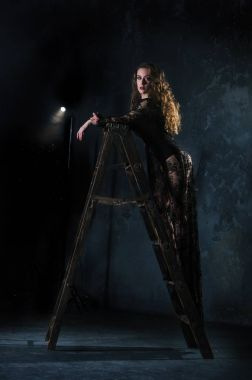 An attractive young woman in a long black dress is standing on a ladder, a ladder against a grunge wall