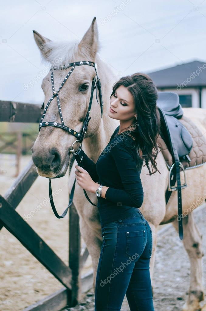 A beautiful woman rider talks to her horse after riding in a country ranch. Lifestyle Photo. Fashion photo