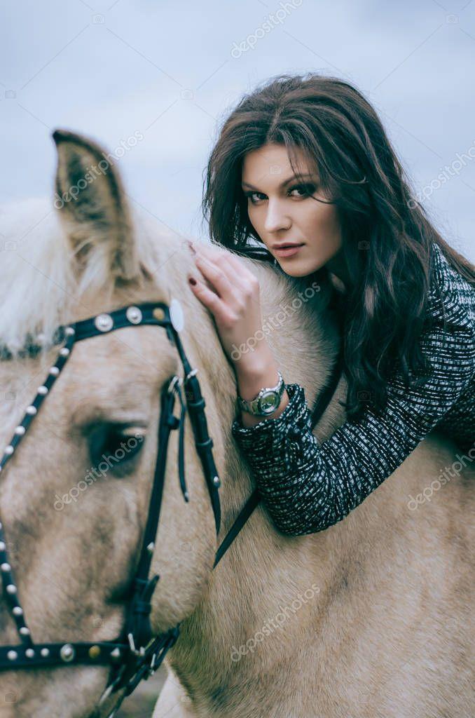 Portrait of a beautiful brunette posing on horseback. Horseback riding. Lifestyle Photo. Fashion photo