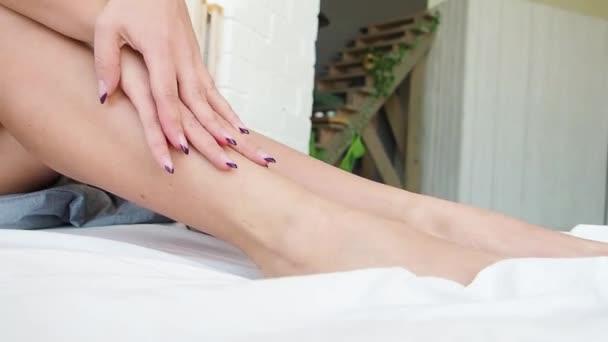 koncept odstraňování vlasů. Detailní záběr ruky krásná žena s manikúra dotýká dlouhé nohy