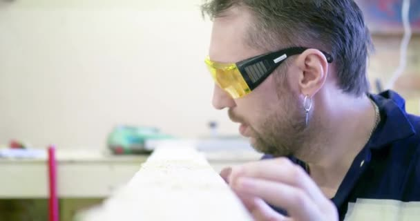 Ein Mann in einer Tischlerei mit Schutzbrille bläst Sägemehl vom Brett und betrachtet die Qualität des Holzes.