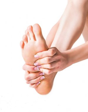 Pain in the foot. Massage of female feet. Isolated on white background.