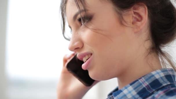 Krásná mladá dívka s tmavými kudrnatými vlasy pomocí její mobilní telefon, venkovní. Portrét uvolněná mladá dáma v letním parku mluví o telefonu