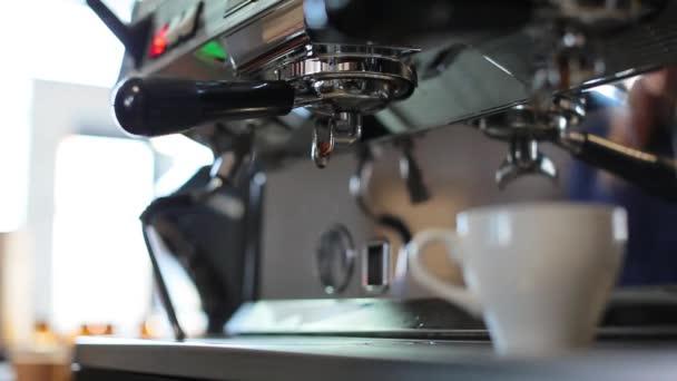 Közelről láthatja, ahogy egy kávéfőző gép kávét tölt egy fehér pohárba.