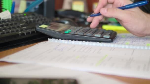 Moderní kancelářský život. Detailní záběry - mužská ruka pracuje na kalkulačce a dělá si poznámky