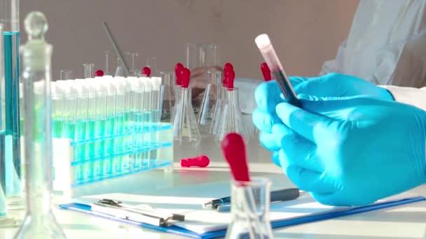 Nahaufnahmen - Arzt hält Reagenzglas mit Blutprobe.