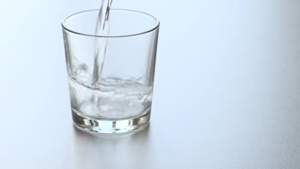 Water is poured into a glass and an effervescent aspirin tablet falls into the water