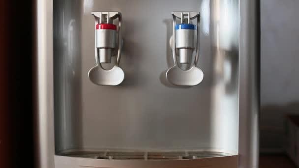 Emberi kéz hideg vizet önt üvegbe a vízadagolóból..