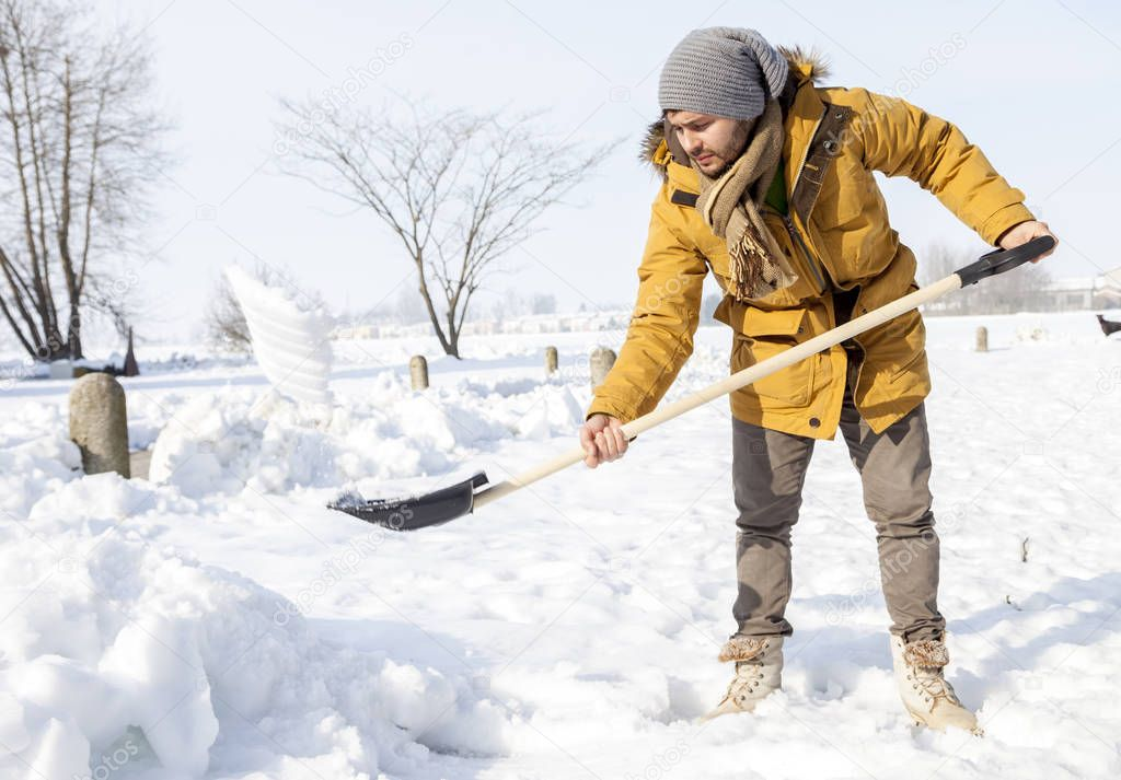 young man shoveling snow in the country
