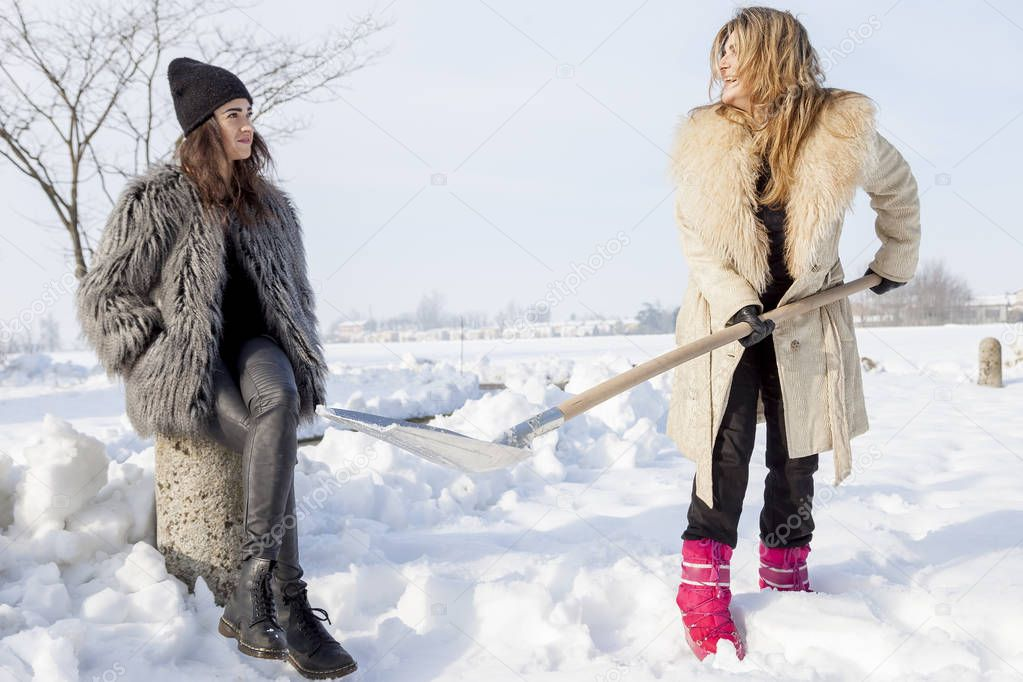 young women shoveling snow near a small wood
