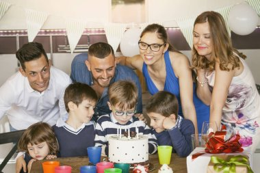 Happy families with children celebrating around a cake for a bir
