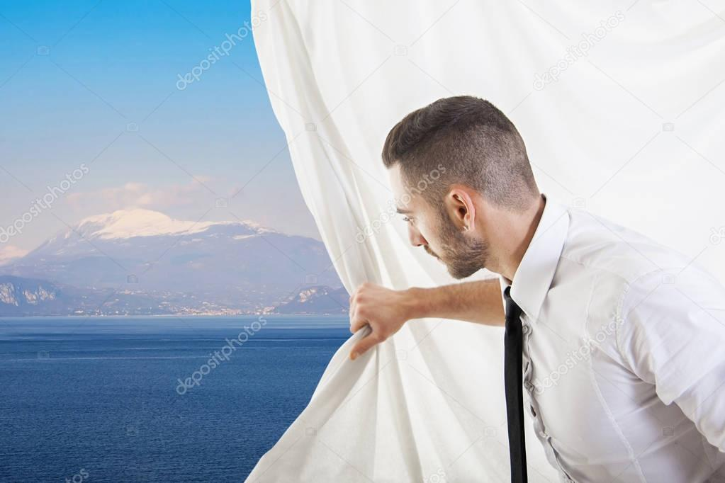 businessman pulls the curtain and discovers a beautiful landscap