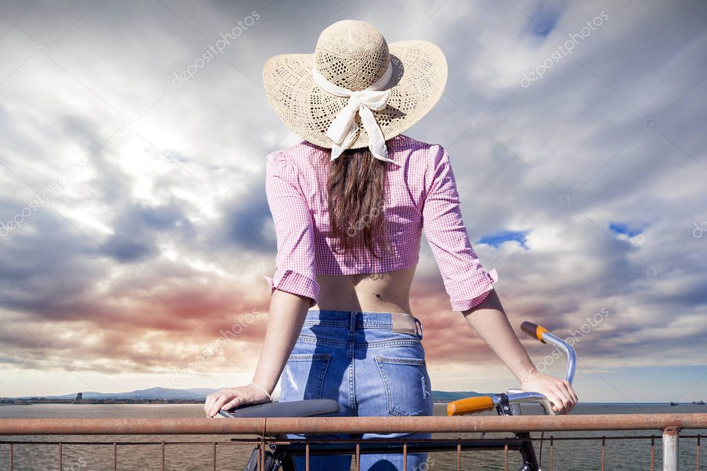 pretty girl with hat from the back looks at sea horizon