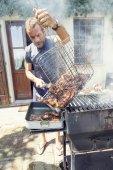 pohledný muž připravuje grilované maso pro přátele venkovní
