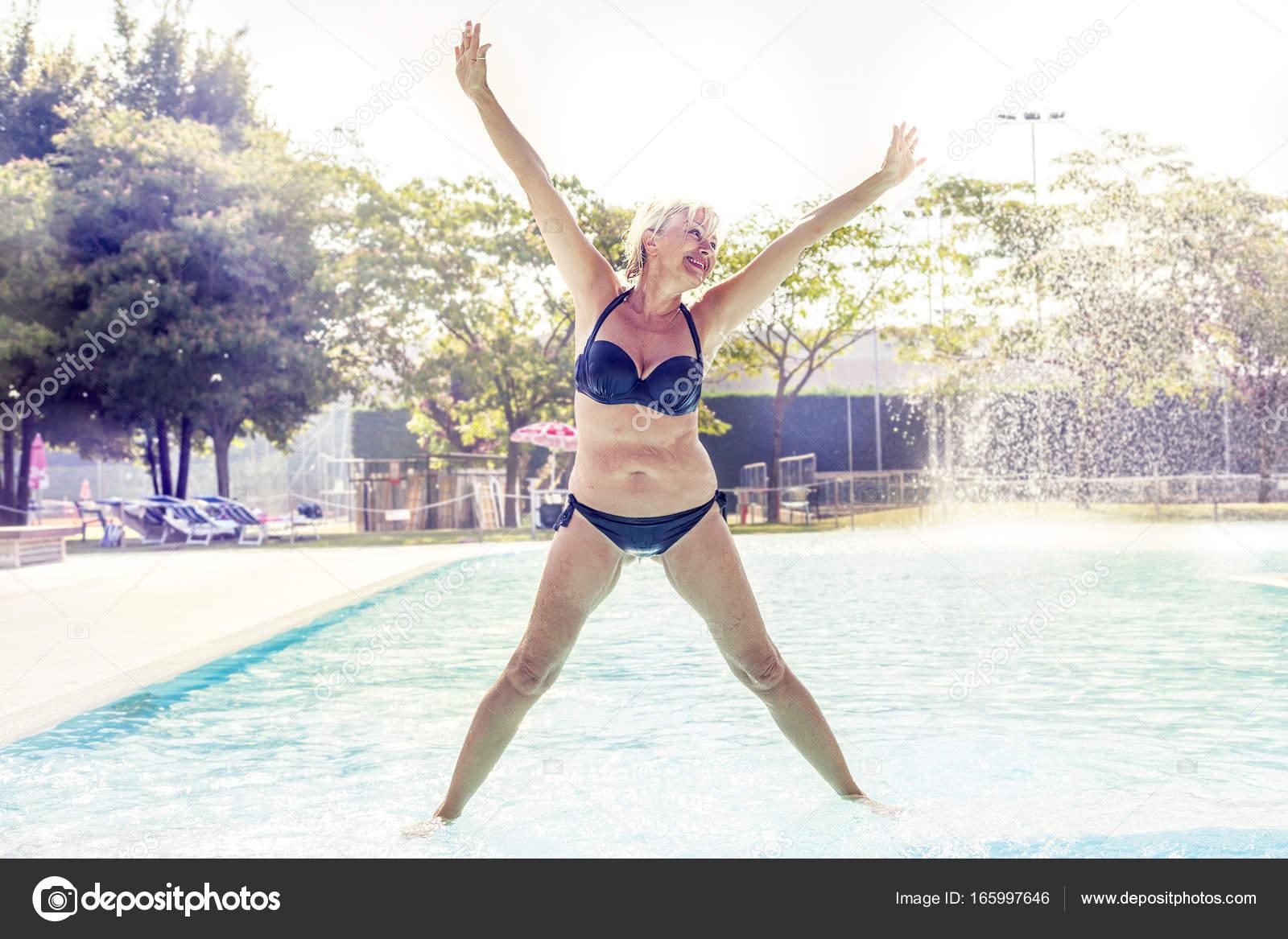 Bella donna matura in costume da bagno fa ginnastica u foto stock