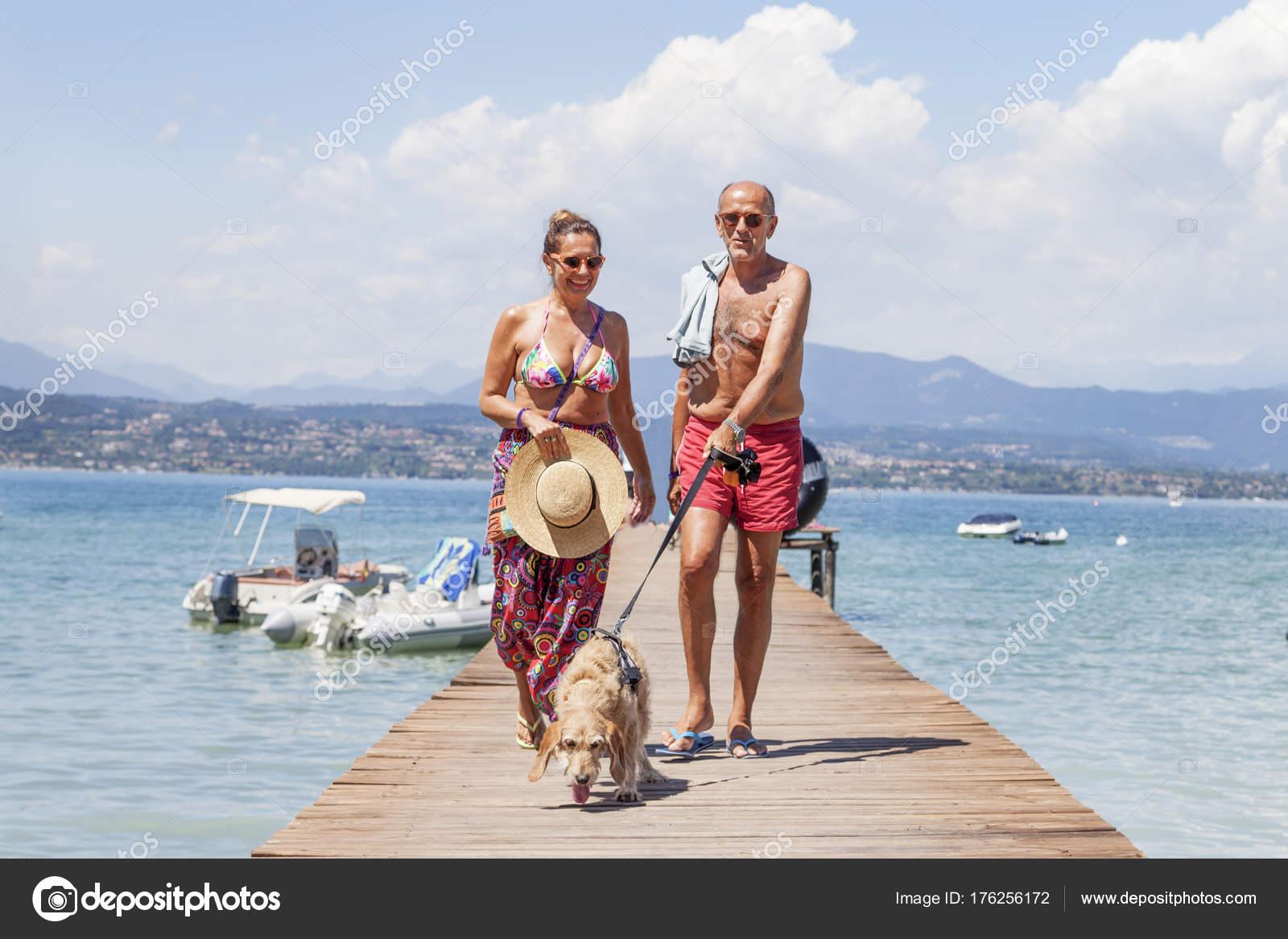 Coppie mature rilassante in costume da bagno cammina con un cane