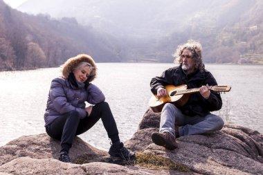beautiful mature couple playing a guitar sitting on the lake