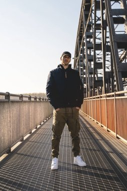 portrait of young rapper posing under a metal bridge