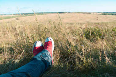 Legs in red shoes on the grass to rest during the hike