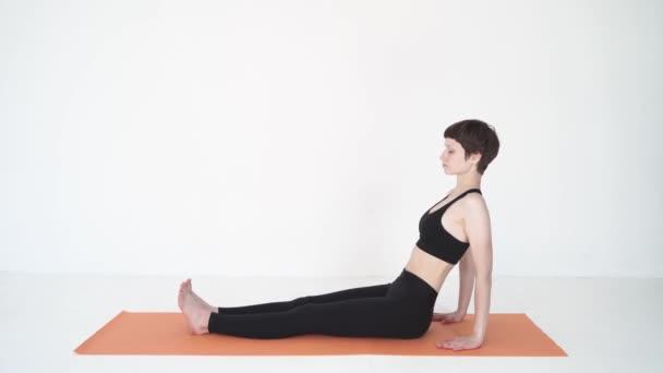 Junge Frau macht Yoga Bridge Pose purvottanasana in weißem Studio