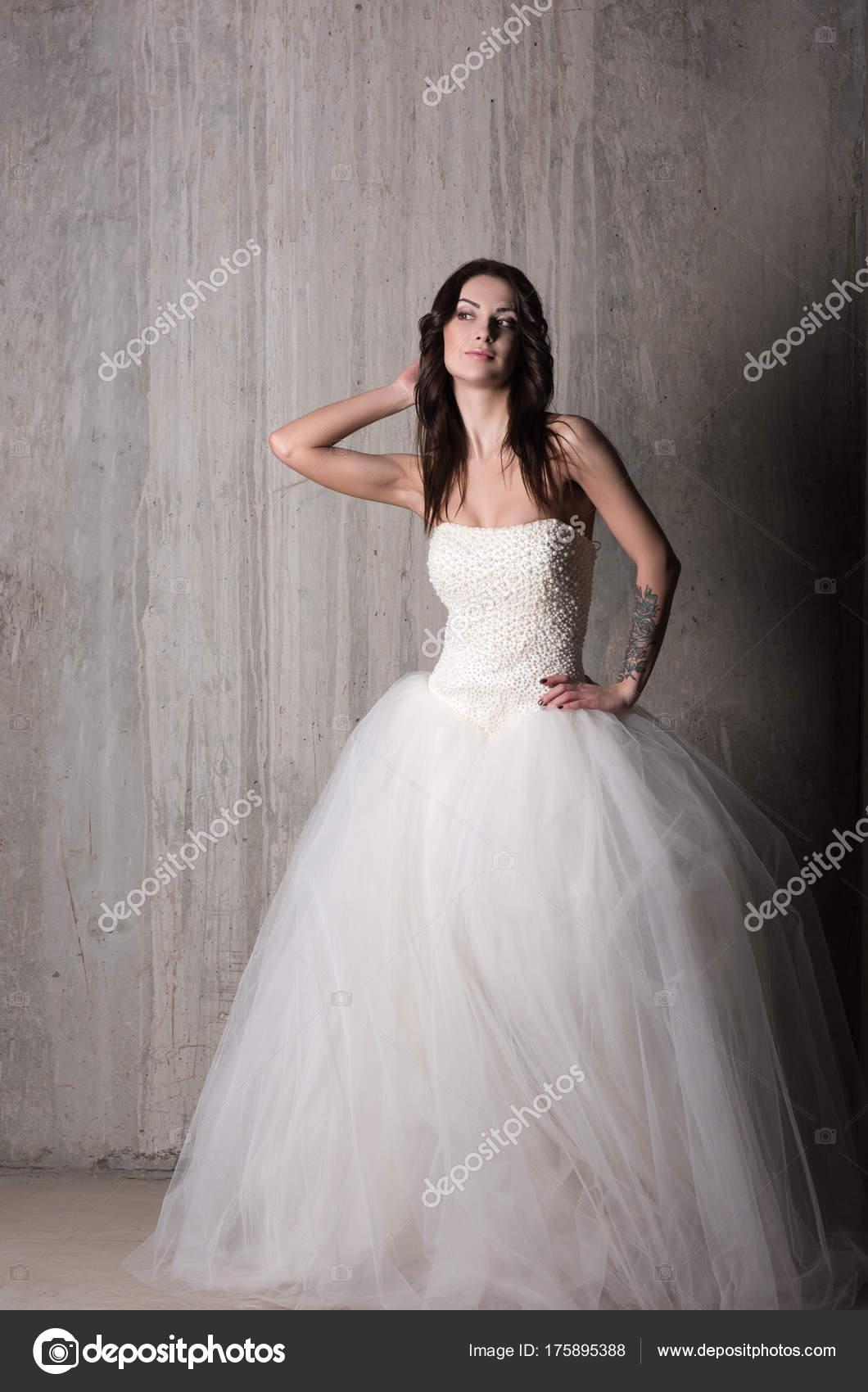 Braut Im Schonen Hochzeitskleid Mit Aus Der Schulter Posen Gegen Die