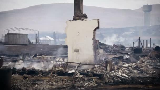 Zbytky spálených domu v kouři. Pohled na komíny a zbytky spálených domů systém vytápění. Pohled ze spálené vesnice