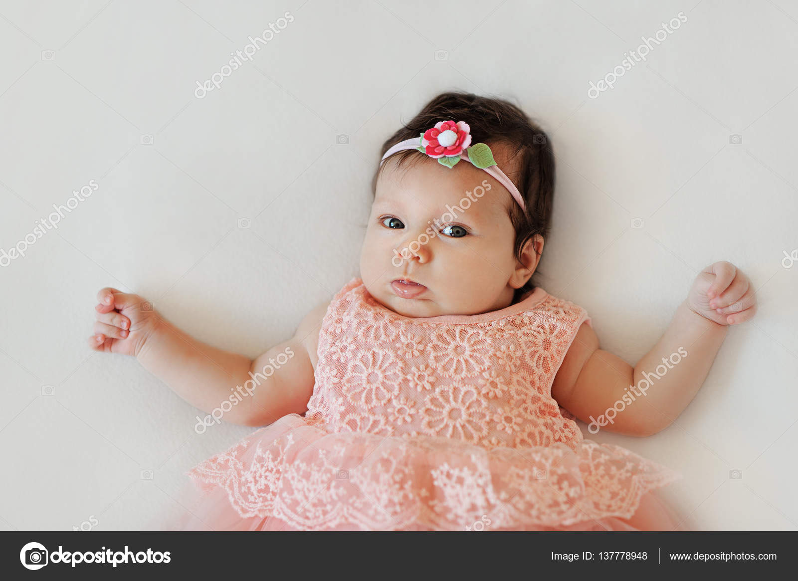 small very cute wide-eyed smiling baby girl in a pink dress lying in