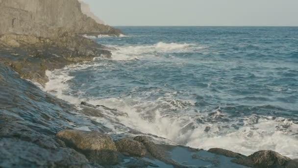 Óceán, kék víz hullámok összeomlik a vulkáni kőzetek.