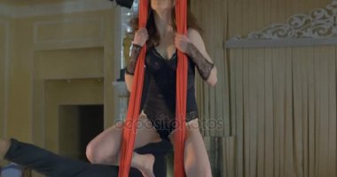 Pair of dancers on red aerial silk, aerial contortion.