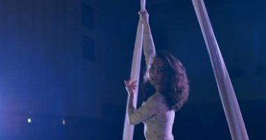 Woman dancer on white aerial silk, aerial contortion.